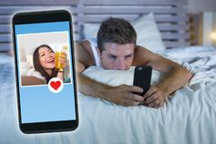 Junger attraktiver Mann, der im Bett auf der Linie suchen nach Sex oder der Liebe findet ein schönes Mädchenprofil wie, die Anwen lizenzfreie stockfotografie