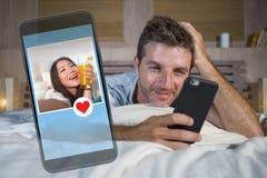 Junger attraktiver Mann, der im Bett auf der Linie suchen nach Sex oder der Liebe findet ein schönes Mädchenprofil wie, die Anwen lizenzfreie stockfotos