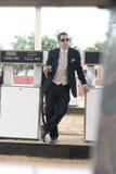 Junger attraktiver Mann in der Klage, die an der Tankstelle steht Stockfotos