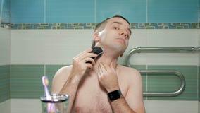 Junger Attraktiver Mann, Der Mit Einem Elektrorasierer Im Badezimmer ...