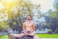 Junger attraktiver Mann, der nachdenklich im Lotussitz auf einem Felsen im Park und in den Blicken zur Seite sitzt Lizenzfreie Stockbilder