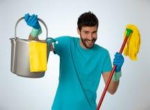 Junger attraktiver Mann, der Reinigungswerkzeuge und Produkte im Eimer lokalisiert im blauen Hintergrund h?lt stockfotografie