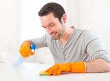 Junger attraktiver Mann, der seine Wohnung säubert lizenzfreies stockfoto