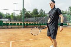 Junger attraktiver Mann, der Tennis am Gericht spielt und auf Ballumhüllung wartet stockfotos