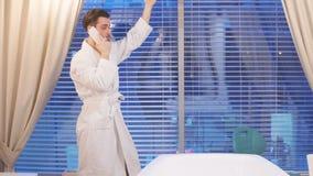 Junger attraktiver Mann in der wei?en Robe, die in einer Luxusbadekurortmitte stillsteht stock footage