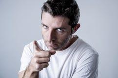 Junger attraktiver Mann mit den blauen Augen, die verärgert und im Rasereigefühl und -umkippen wütend schauen stockbild