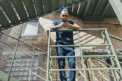 Junger attraktiver Mann mit den blauen Dreadlocks, die am Treppenhaus stehen stockfotos