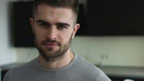 Junger attraktiver Mann mit den grauen Augen, die direkt auf einer Kamera schauen stock footage