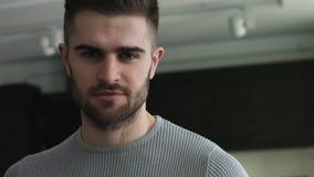 Junger attraktiver Mann mit den grauen Augen, die direkt auf einer Kamera schauen stock video