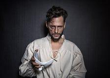 Junger attraktiver Mann mit Gesichtsnarben und einer weißen Maske, gekleidet in einem Phantom des Opernblickes lizenzfreie stockfotografie