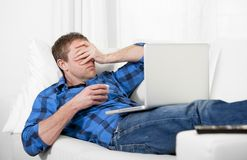 Junger attraktiver Mann mit Kopfschmerzen und Druck unter Verwendung des Computers Lizenzfreie Stockfotos