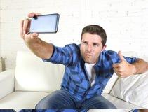 Junger attraktiver Mann 30s, der zu Hause selfie Bild oder Selbstvideo mit dem Handy sitzt auf dem Couchlächeln glücklich nimmt Lizenzfreie Stockfotografie