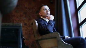 Junger attraktiver Mann sitzt auf dem Retro- Stuhl vor dem Fenster und sützt Hand sein Kinn stock footage