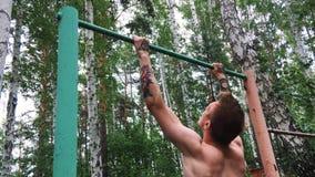 Junger attraktiver Mann tut Übung auf dem Barren draußen Der hemdlose Kerl nimmt an Amateursport teil aktiv stock video footage