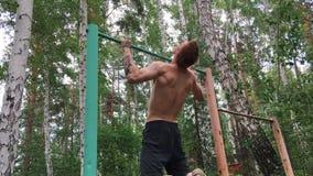 Junger attraktiver Mann tut Übung auf dem Barren draußen Der hemdlose Kerl nimmt an Amateursport teil aktiv stock footage