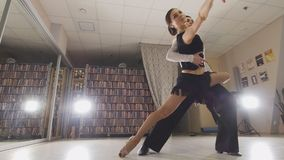 Junger attraktiver Mann und Frau, die lateinamerikanischen Tanz in den Kostümen im Studio, Fokus auf Füßen, Ansicht von tanzt lizenzfreies stockbild
