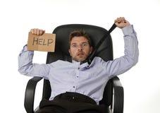 Junger attraktiver müder und vergeudeter Geschäftsmann, der auf dem Bürostuhl bittet um Hilfe im Druck sitzt Stockfotos