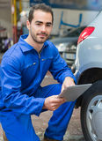 Junger attraktiver Mechaniker, der an einem Auto an der Garage arbeitet Lizenzfreie Stockfotografie