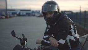 Junger attraktiver Motorradfahrer mit schwarzem Sturzhelm auf Straße Mannmotorradradfahrer stock footage