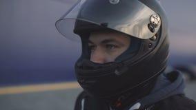 Junger attraktiver Motorradfahrer mit schwarzem Sturzhelm auf Straße Mannmotorradradfahrer stock video footage