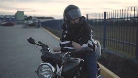 Junger attraktiver Motorradfahrer mit schwarzem Sturzhelm auf Straße Mannmotorradradfahrer stock video