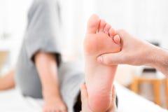 Junger attraktiver Physiotherapeut, der Reflexzonenmassage auf einem Patienten tut stockbilder