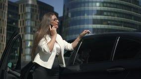 Junger attraktiver Rechtsanwalt, der am Telefon steht auf Hintergrund des Autos und der Gebäude spricht stock video footage