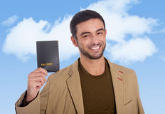 Junger attraktiver Reisendmann, der das Passlächeln glücklich und überzeugt hält stockfoto