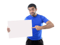 Junger attraktiver Sportmann, der leere Anschlagtafel als Kopienraum hält Stockbilder