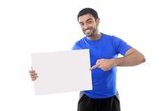 Junger attraktiver Sportmann, der leere Anschlagtafel als Kopienraum hält Stockfotos