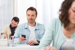 Junger attraktiver Student, der sein Mobile während der Klassen verwendet Stockfoto