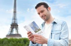 Junger attraktiver Tourist, der einen Führer von Paris liest Lizenzfreie Stockfotografie