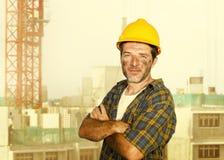 Junger attraktiver und überzeugter Auftragnehmer- oder Bauarbeitermann mit dem Erbauerschutzhelm, der das Unternehmenslächeln net stockfotografie