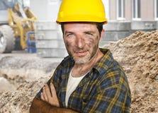 Junger attraktiver und überzeugter Auftragnehmer- oder Bauarbeitermann mit dem Erbauerschutzhelm, der das Unternehmenslächeln net stockbild
