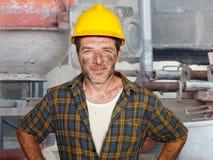 Junger attraktiver und überzeugter Auftragnehmer- oder Bauarbeitermann mit dem Erbauerschutzhelm, der das Unternehmenslächeln net lizenzfreie stockfotos