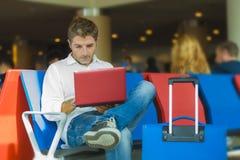 Junger attraktiver und entspannter Reisendmann mit dem Gepäck, das mit Laptop-Computer Warteflug am Flughafenabfahrtaufenthaltsra lizenzfreie stockfotos