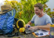 Junger attraktiver und glücklicher digitaler Nomademann, der draußen mit Laptop-Computer netter und überzeugter laufender Geschäf stockfotografie