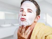 Junger attraktiver und gl?cklicher homosexueller Mann im Badezimmer unter Verwendung der Sch?nheitspapier-Gesichtsmaske, die sein lizenzfreies stockbild