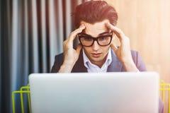 Junger attraktiver und hübscher Geschäftsmann, der an dem Computerlaptop sitzt am Schreibtisch schaut konzentriert arbeitet Stockbild