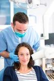 Junger attraktiver Zahnarzt, der eine Radiographie von Frauenzähnen tut Stockbild