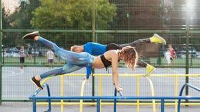 Junger attrective crossfit Mann und Frau, die auf dem sportsground ausarbeitet stockbilder