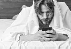 Junger ausdehnender Mann beim morgens aufwachen Ausdehnung nach morgens aufwachen Entspannter Bettmann stockfotografie