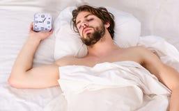 Junger ausdehnender Mann beim morgens aufwachen Netter junger Mann wacht auf, nachdem er morgens geschlafen hat stockbilder