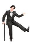 Junger Ausführender im schwarzen Anzug, der einen Stock und ein Tanzen hält Stockbilder