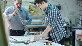 Junger Auszubildender, der einen Rahmen hinter dem Schreibtisch in der Rahmenwerkstatt konstruiert stock video footage