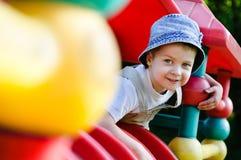 Junger autistischer Junge, der auf Spielplatz spielt Stockfotografie