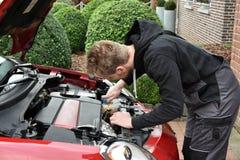 Junger Automechaniker bei der Arbeit stockfoto