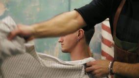 Junger bärtiger Friseur, der Salonkap vom stilvollen Kunden mit Durchdringen in seinem Ohr und in tatoo entfernt erfüllt stock video footage
