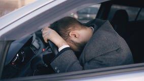 Junger bärtiger Geschäftsmann, der im Auto sehr umgekippt und nach vollständigem Systemausfall betont sitzt und in Stau umzieht stockfotografie