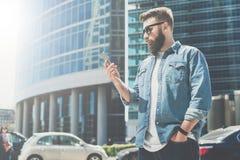 Junger bärtiger Geschäftsmann in der Sonnenbrille steht auf Stadtstraße und benutzt Smartphone Im Hintergrund ist modernes Gebäud Lizenzfreies Stockbild